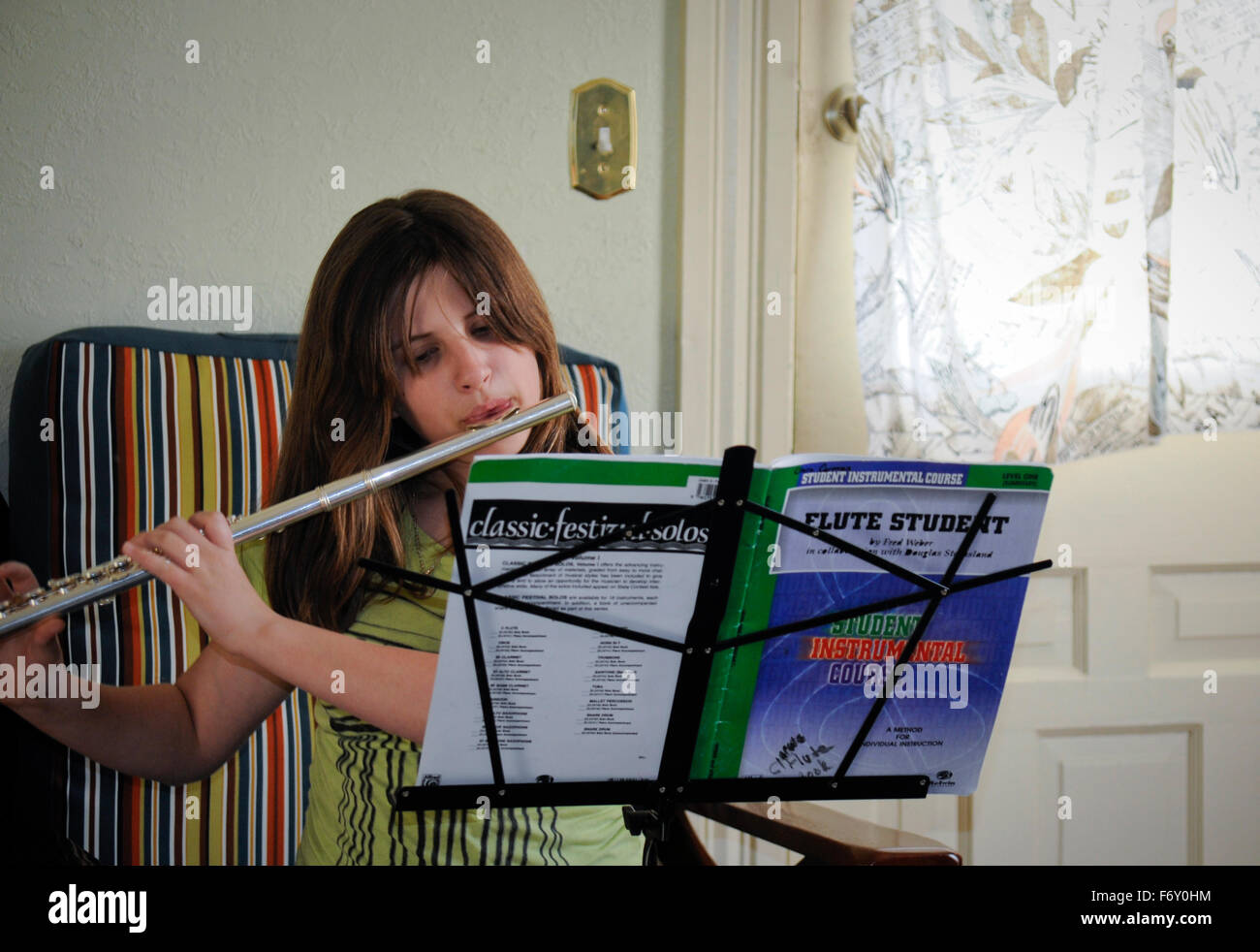 Pre-teen girl 12 years old practicing her clarinet for the school band. Indiana - Stock Image