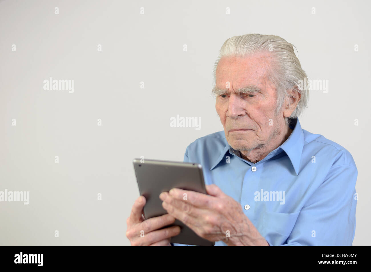 Elderly man with blue shirt holding a modern tablet PC while looking at it with a nostalgic facial expression in - Stock Image