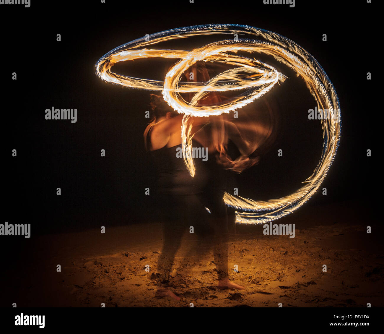 Fire twirling or 'fire poi' performance - Stock Image