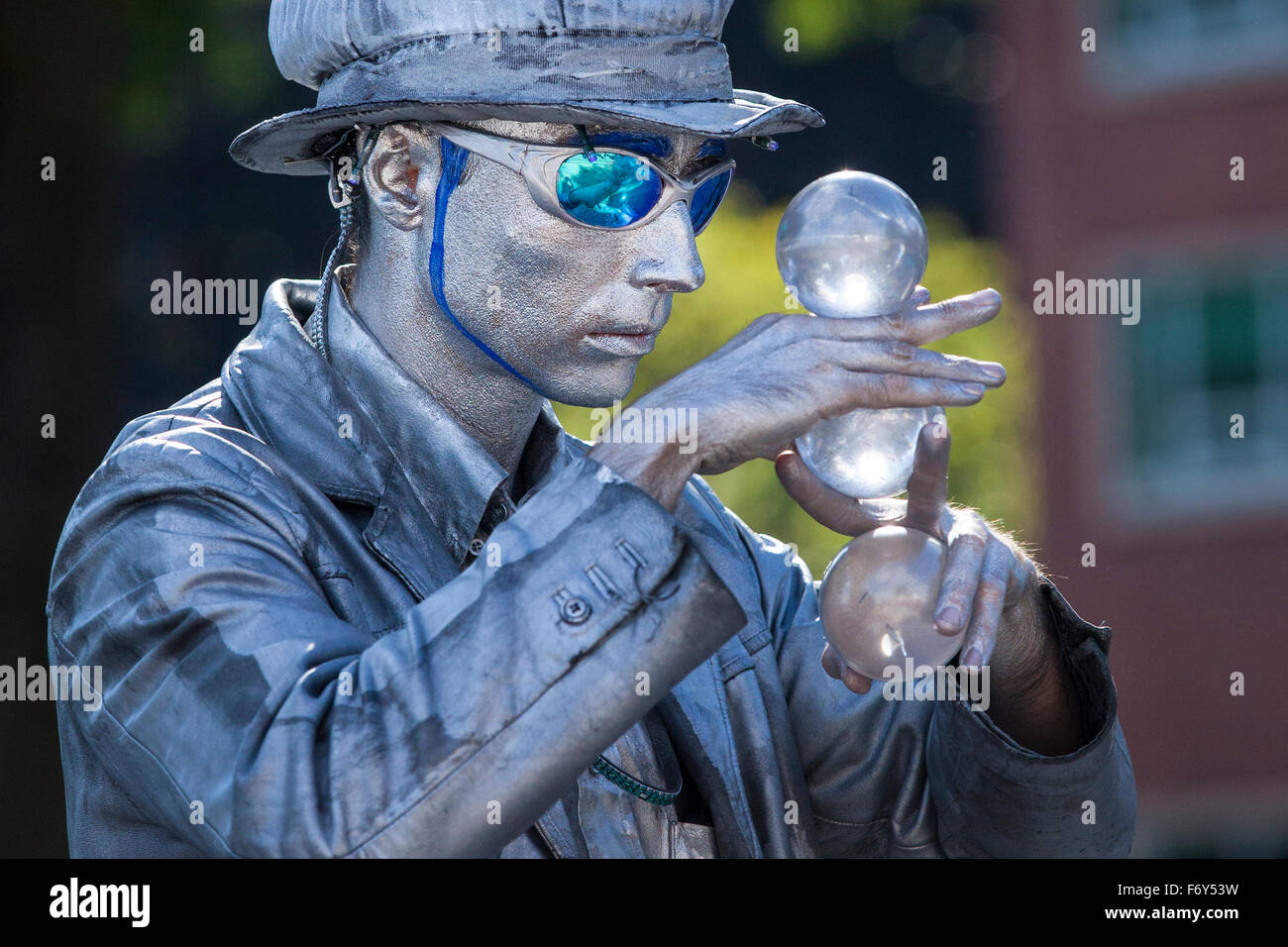 A street performer gazes at large glass marbles during his act at the Saturday Market in Portland, Oregon. - Stock Image