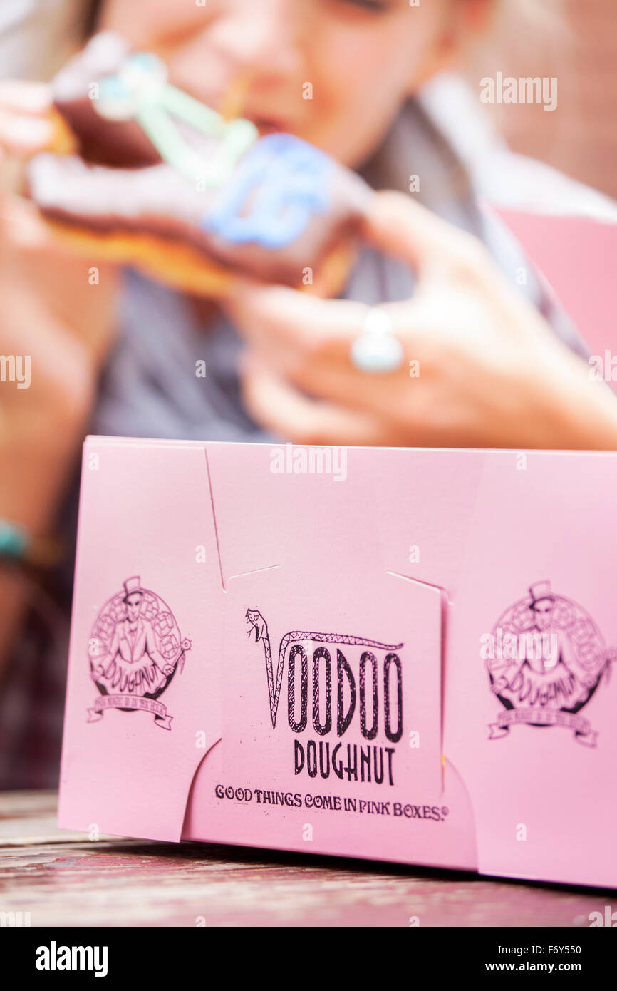 A young woman bites into a pastry from Voodoo Doughnuts in Portland, Oregon, where 'Good things come in pink - Stock Image