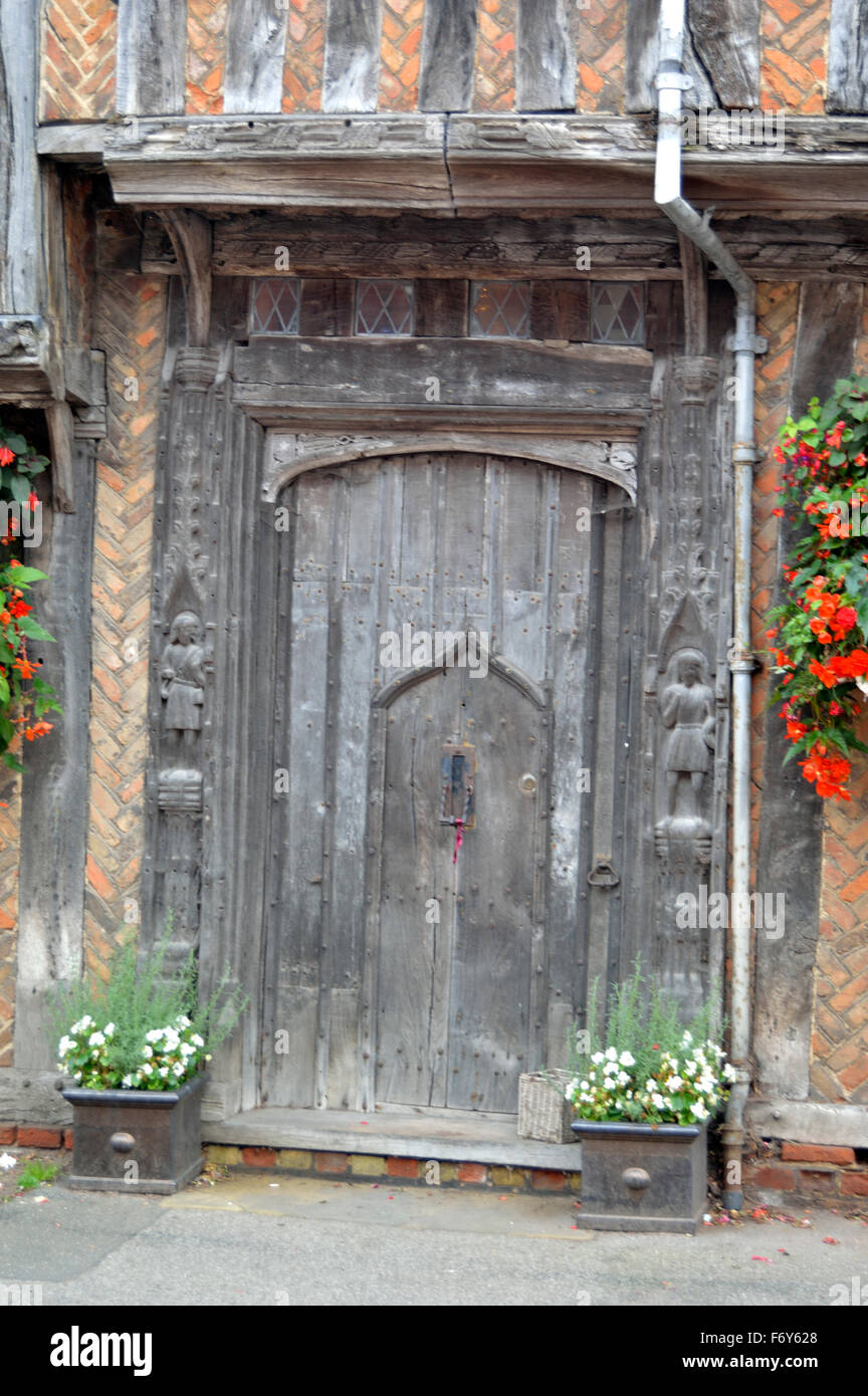 Old door with carvings on a building in Lavenham village in Suffolk, United Kingdom - Stock Image