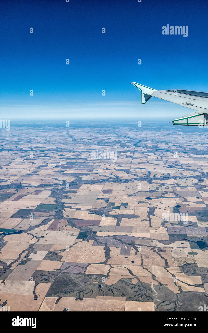 the view,  flying over the Canadian prairies, showing the patchwork for fields, crops, lakes and rivers, and wing - Stock Image