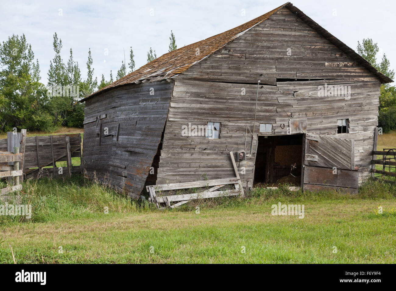 the dilapidated old barn sits on the homestead farm, no longer needed, aged beyond repair, it could be anywhere - Stock Image