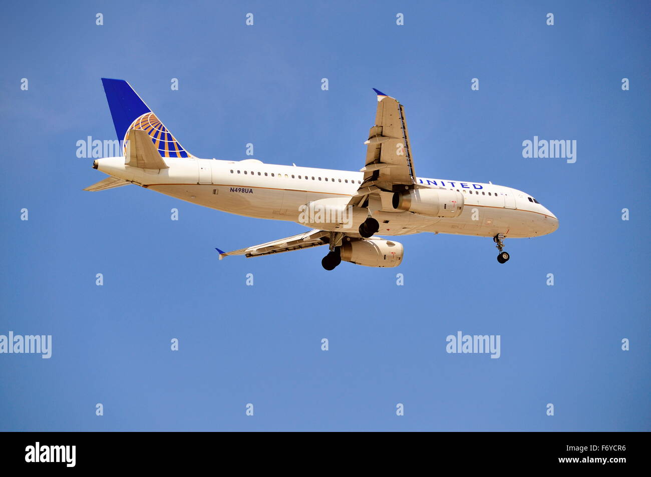 With its landing gear down and locked, a United Airlines Airbus A320 jet makes its final approach before landing - Stock Image