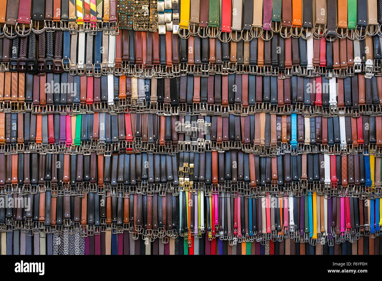 Many colored leather belts on a market. Fashion background - Stock Image
