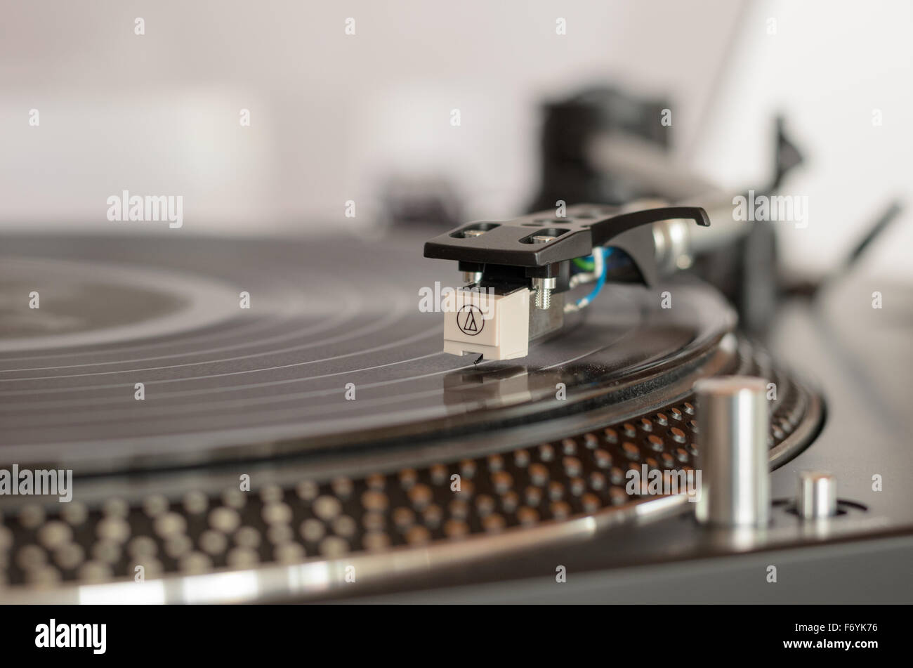Closeup of a retro turntable while playing a vinyl record - Stock Image