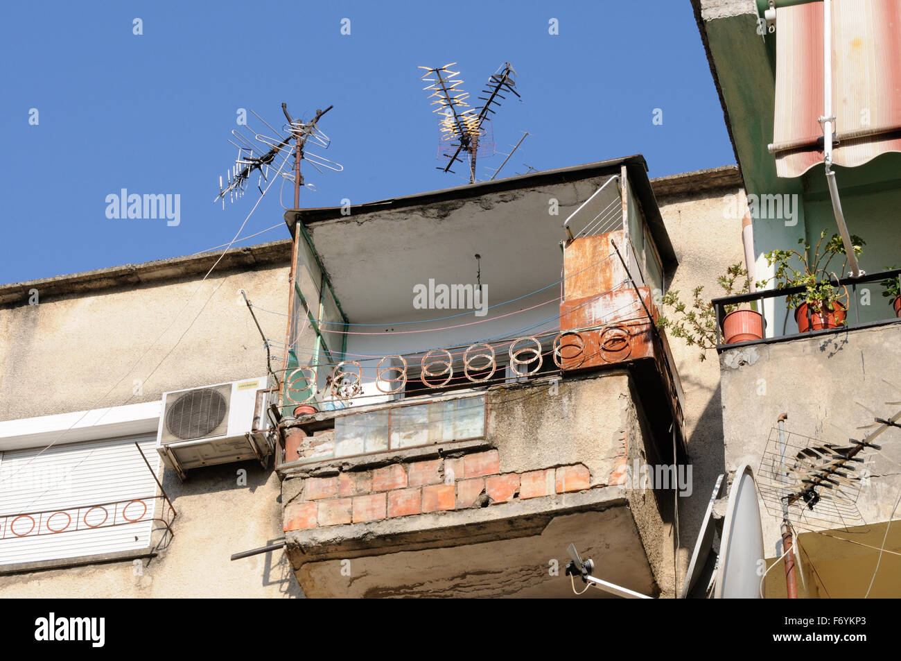 An insecure looking balcony on an old building. Tirana, Albania. - Stock Image