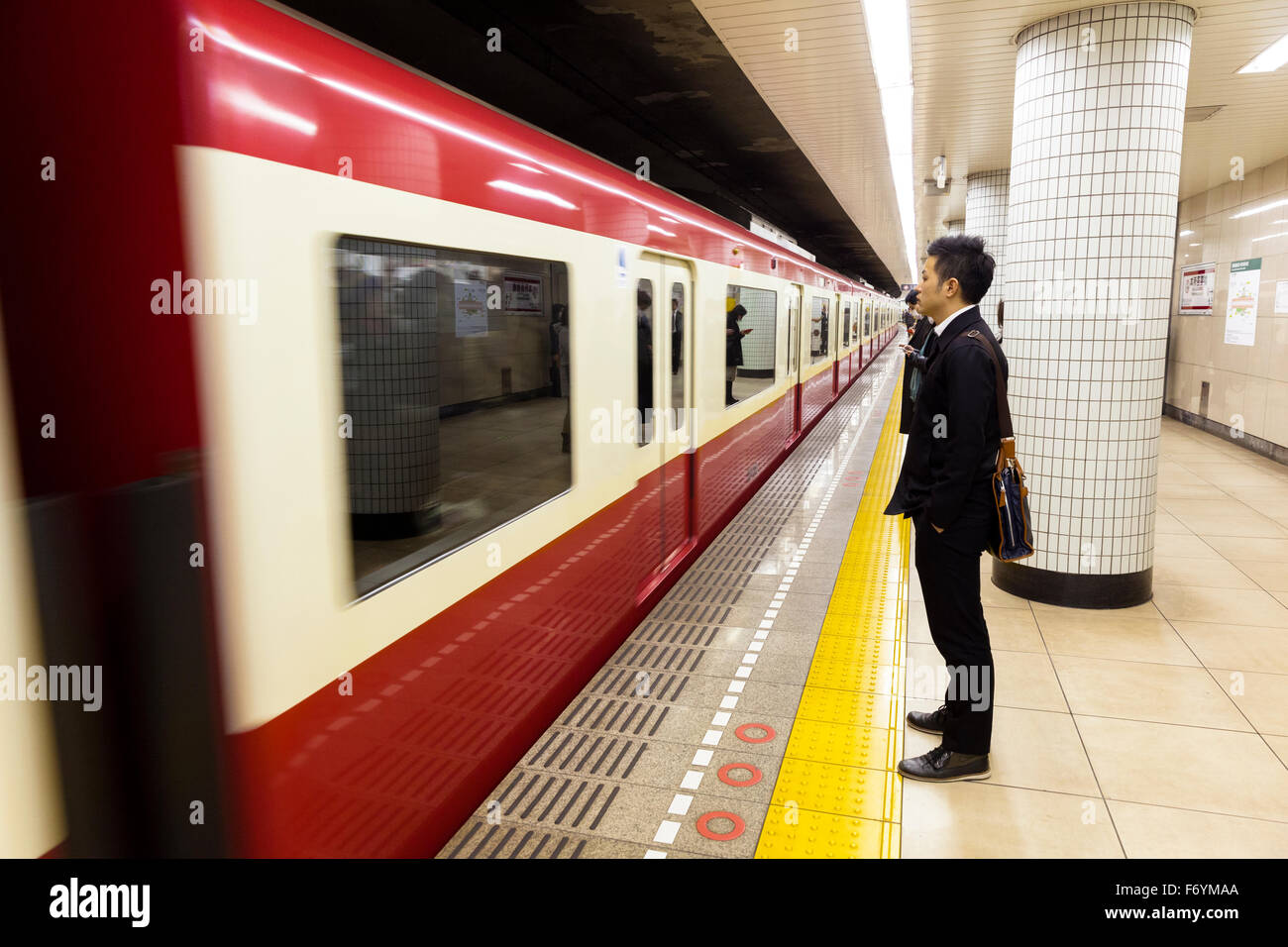 A Japanese man waiting in the underground for a passing train - Stock Image
