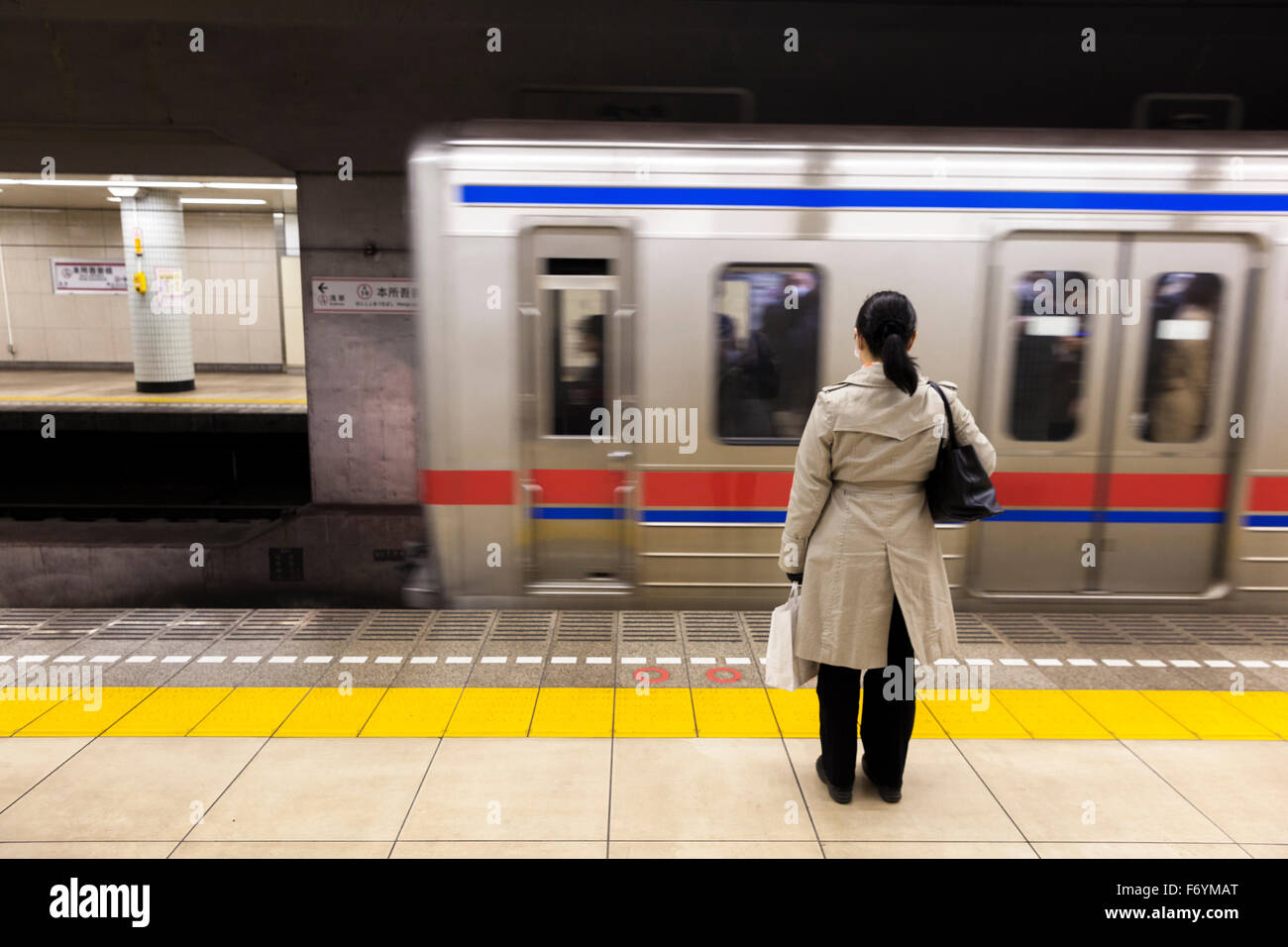 A Japanese woman waiting in the underground for a passing train - Stock Image