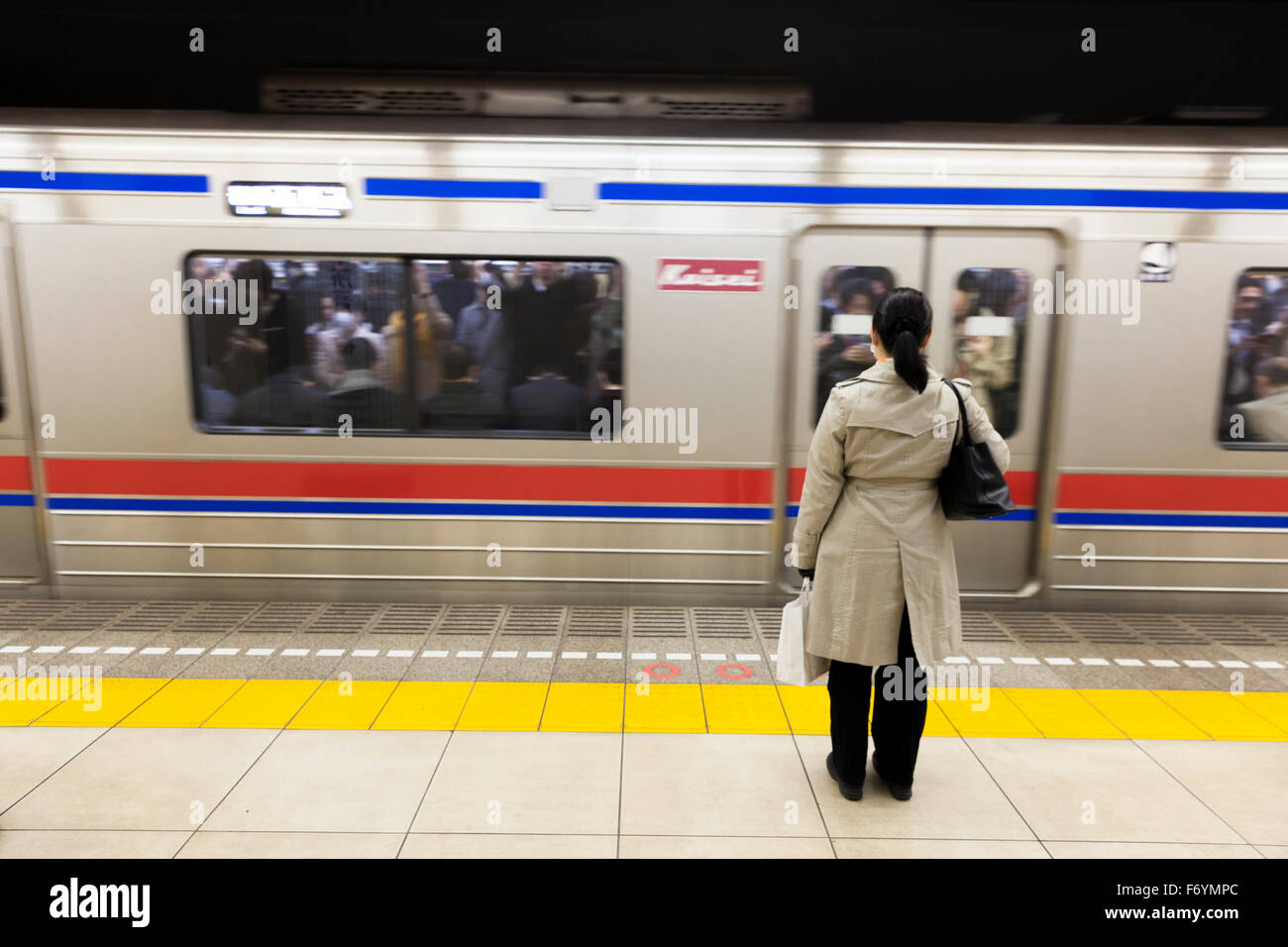 A Japanese woman waiting at the metro for a passing train - Stock Image