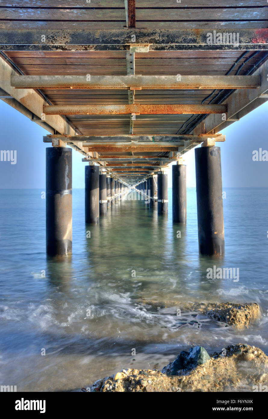 Rusty metallic  pier from sea level in vertical composition creating a diagonal directive tunnel. - Stock Image