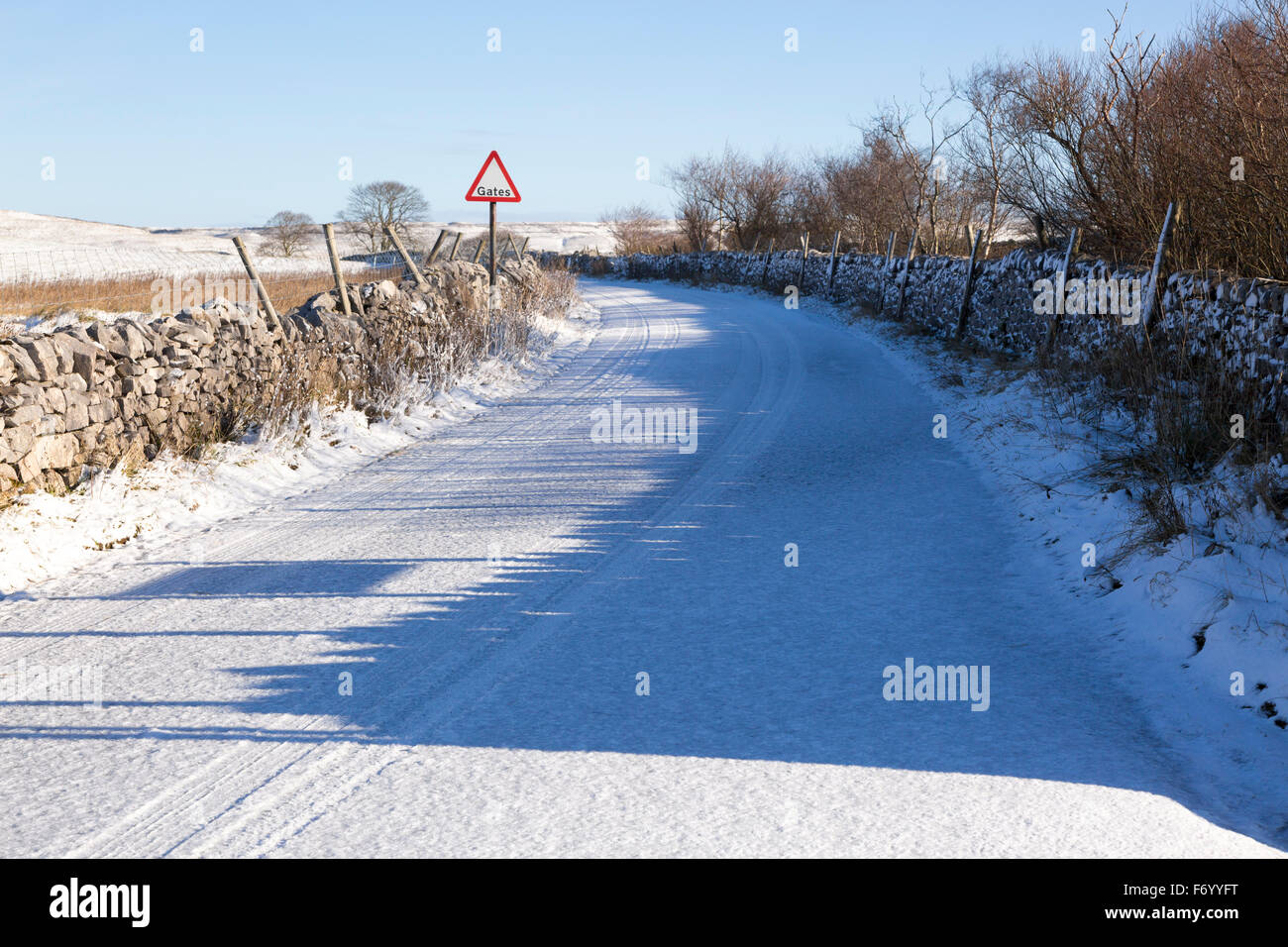 Snow covered road on Malham Moor in winter with a warning sign - Stock Image