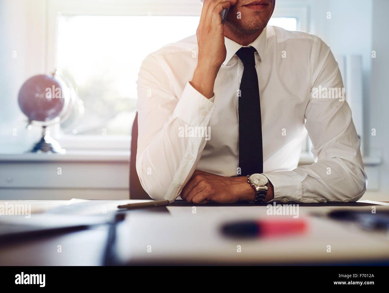 Close up of business man sitting at his desk talking on the phone - Stock Image