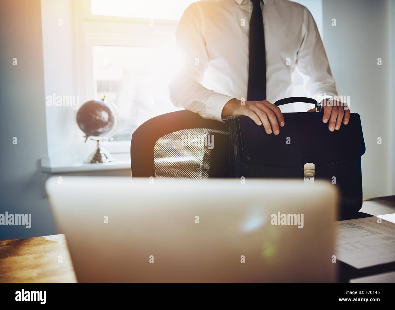 Business concept, man standing at desk with briefcase and laptop wearing a classic business outfit - Stock Image