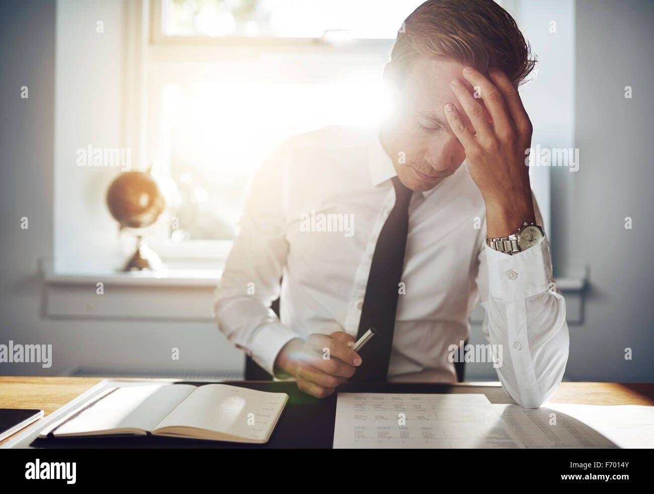 Business man working concentrated on documents looking tired holding his hand to his forehead - Stock Image