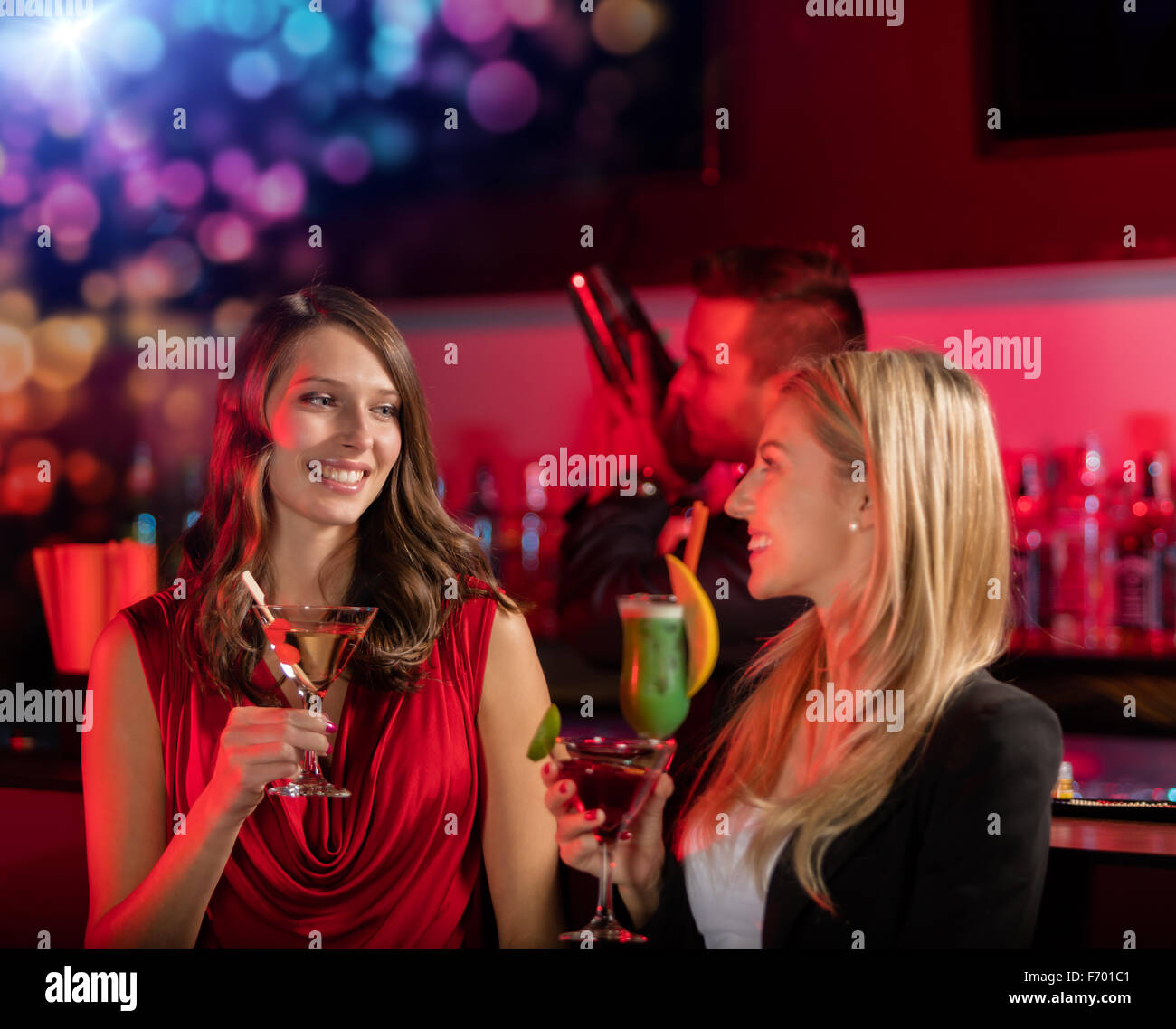 Two girls at the bar with cocktail drink - Stock Image