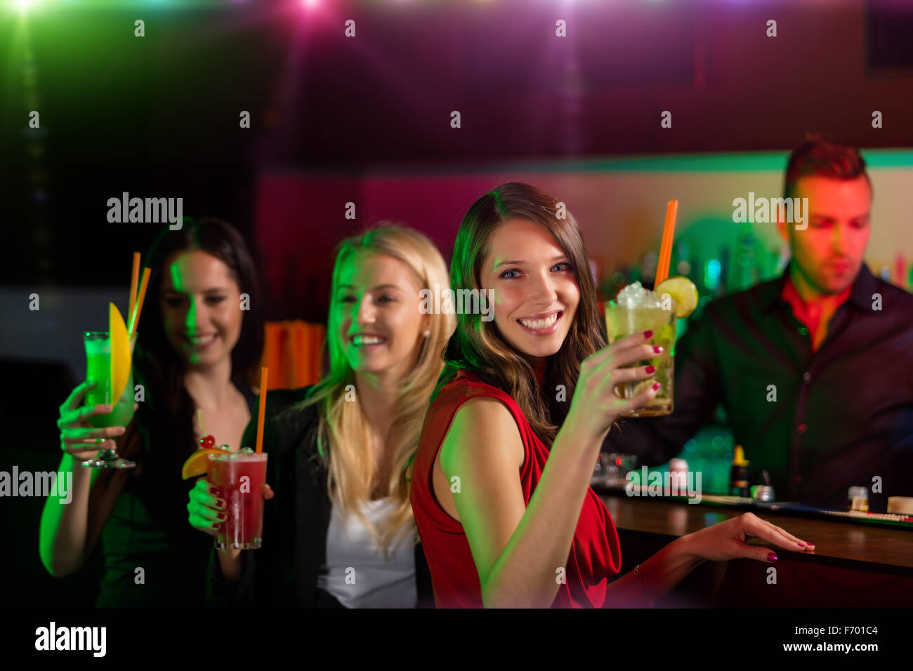 Young friends drinking cocktails together at party - Stock Image