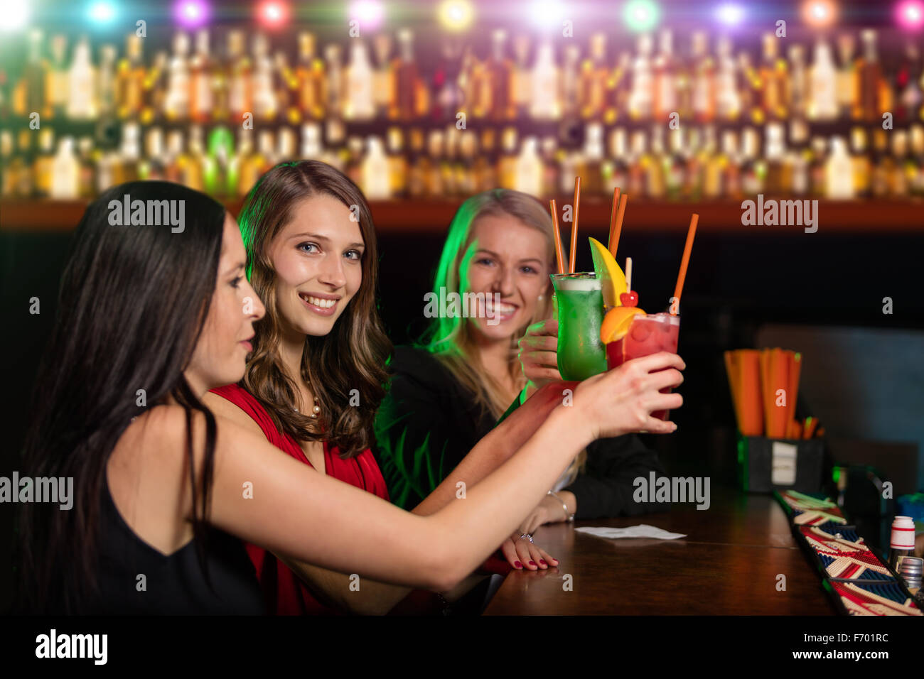 Group of friends at the bar raising their glass of cocktals - Stock Image