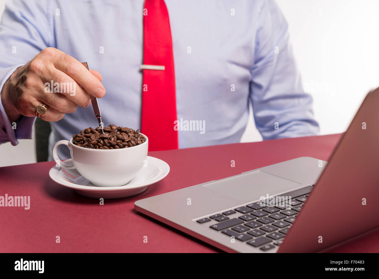 Male in office surroundings stirring a cup containing strong arabica coffee beans. concept strong morning coffee - Stock Image
