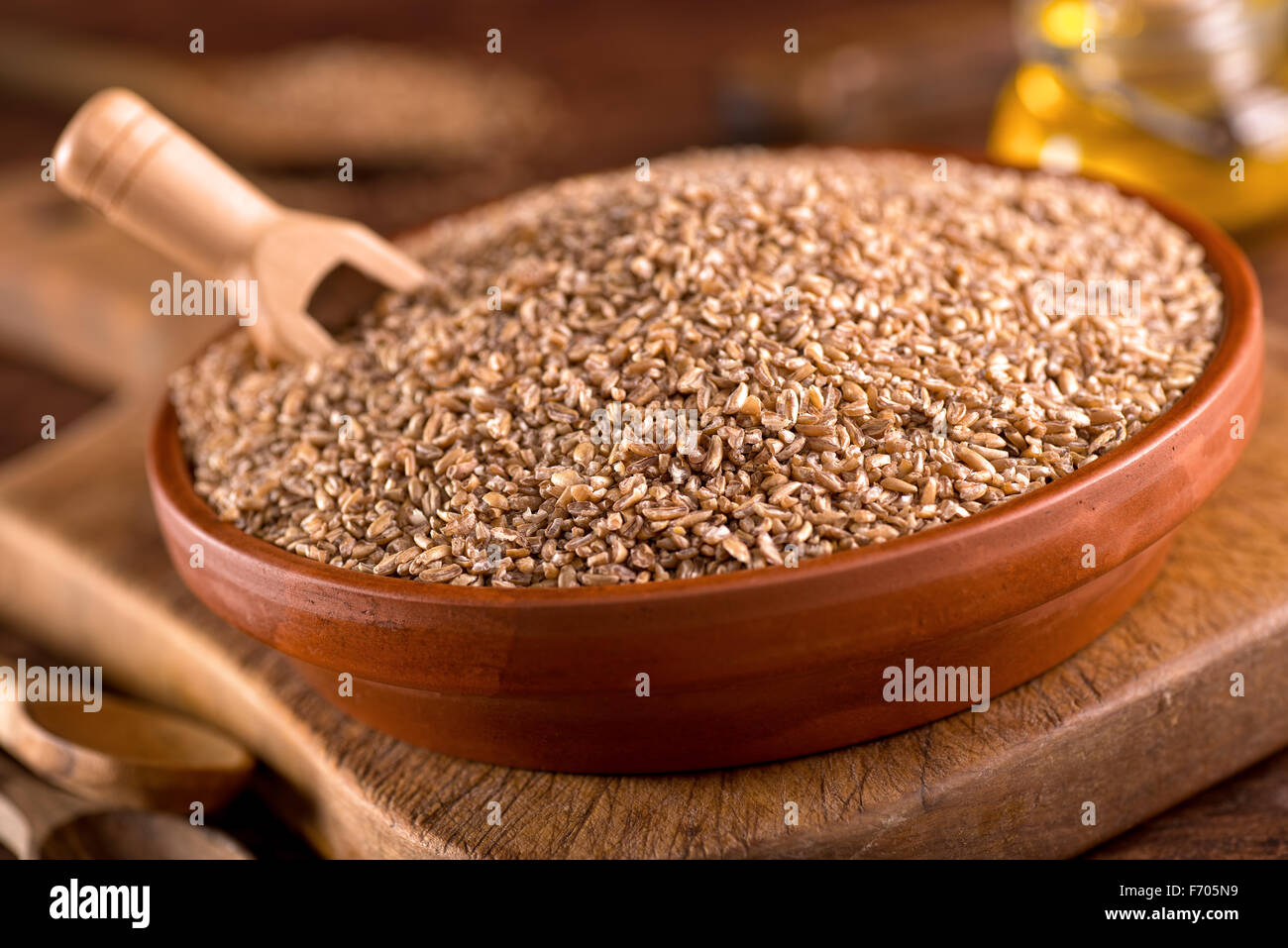 A bowl of raw bulgar wheat against a rustic background. - Stock Image