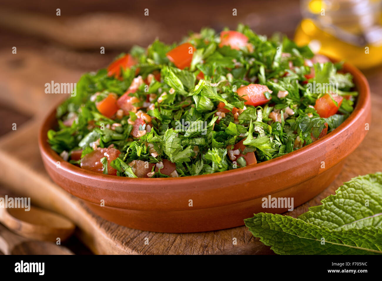 A bowl of delicious fresh tabouli with parsley, mint, tomato, onion, olive oil, lemon juice, and bulgar wheat. - Stock Image