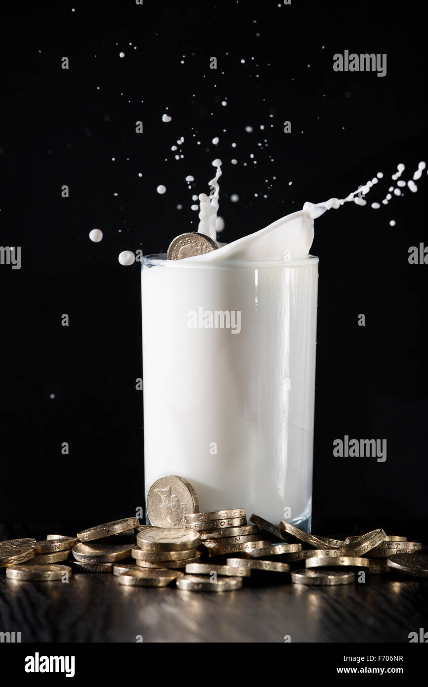 A pound coin dropped into a glass of milk on a table piled with money. - Stock Image
