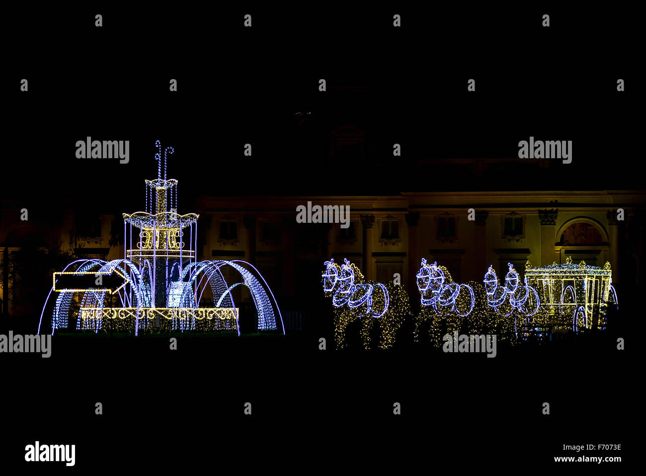 Illumination of Fountain and Horses with Carriage in Front of Building - Stock Image