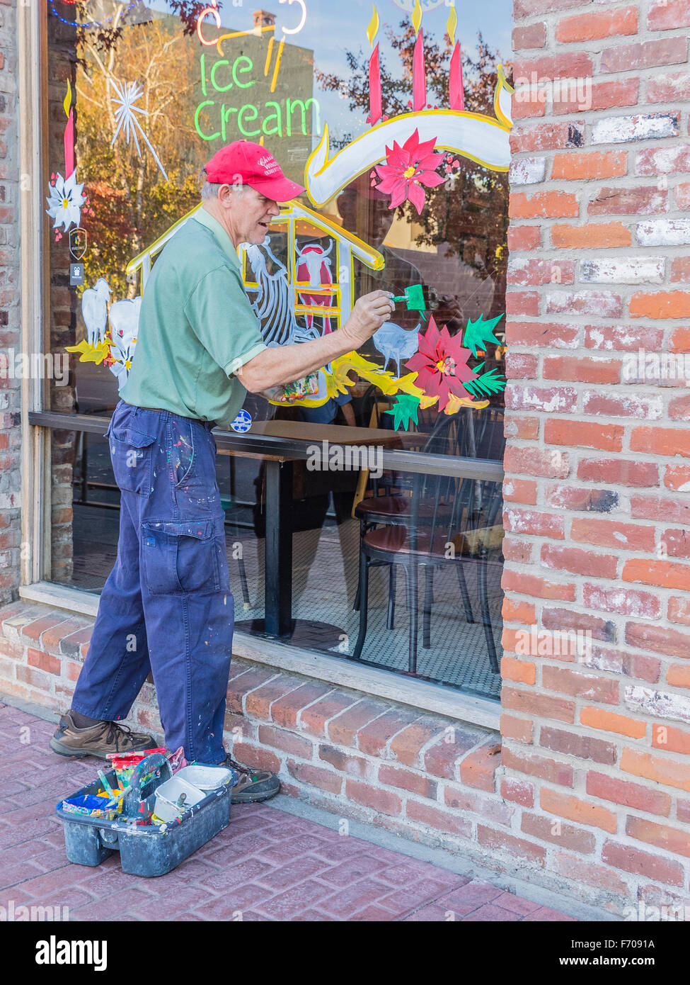 A Christmas window painter stands outside of a store window he is in the process of painting and holds his brush - Stock Image