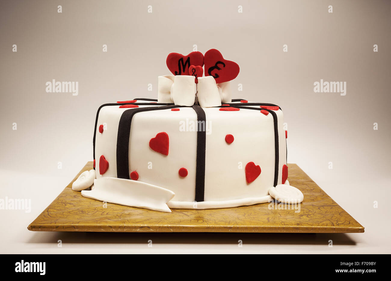 Anniversary cake decoration with red hearts and black ribbons. - Stock Image