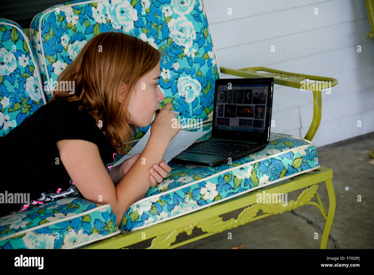 Pre-teen girl using the internet on laptop to design a drawing Stock Photo