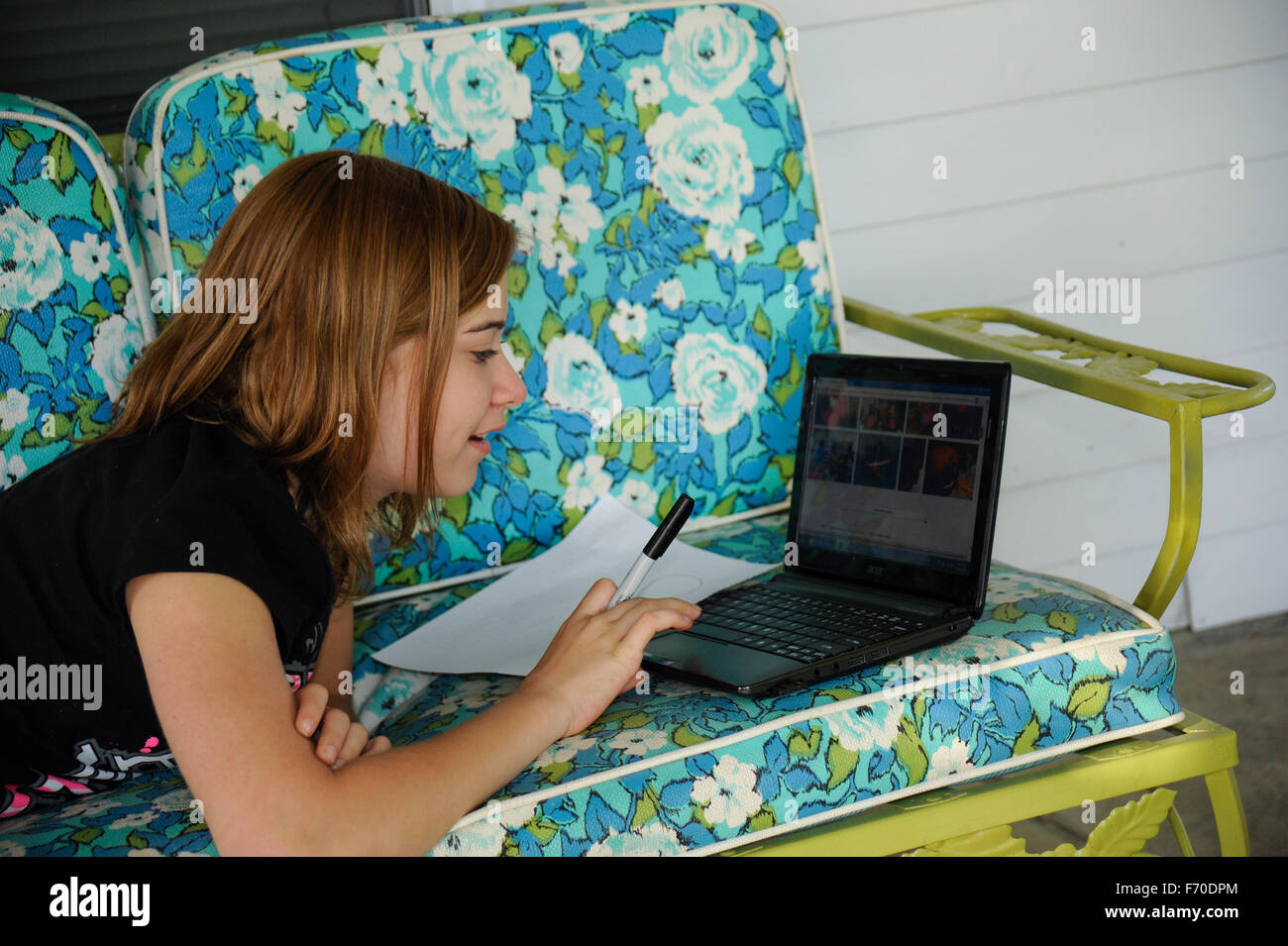 Pre-teen girl using the internet on laptop to design a drawing - Stock Image