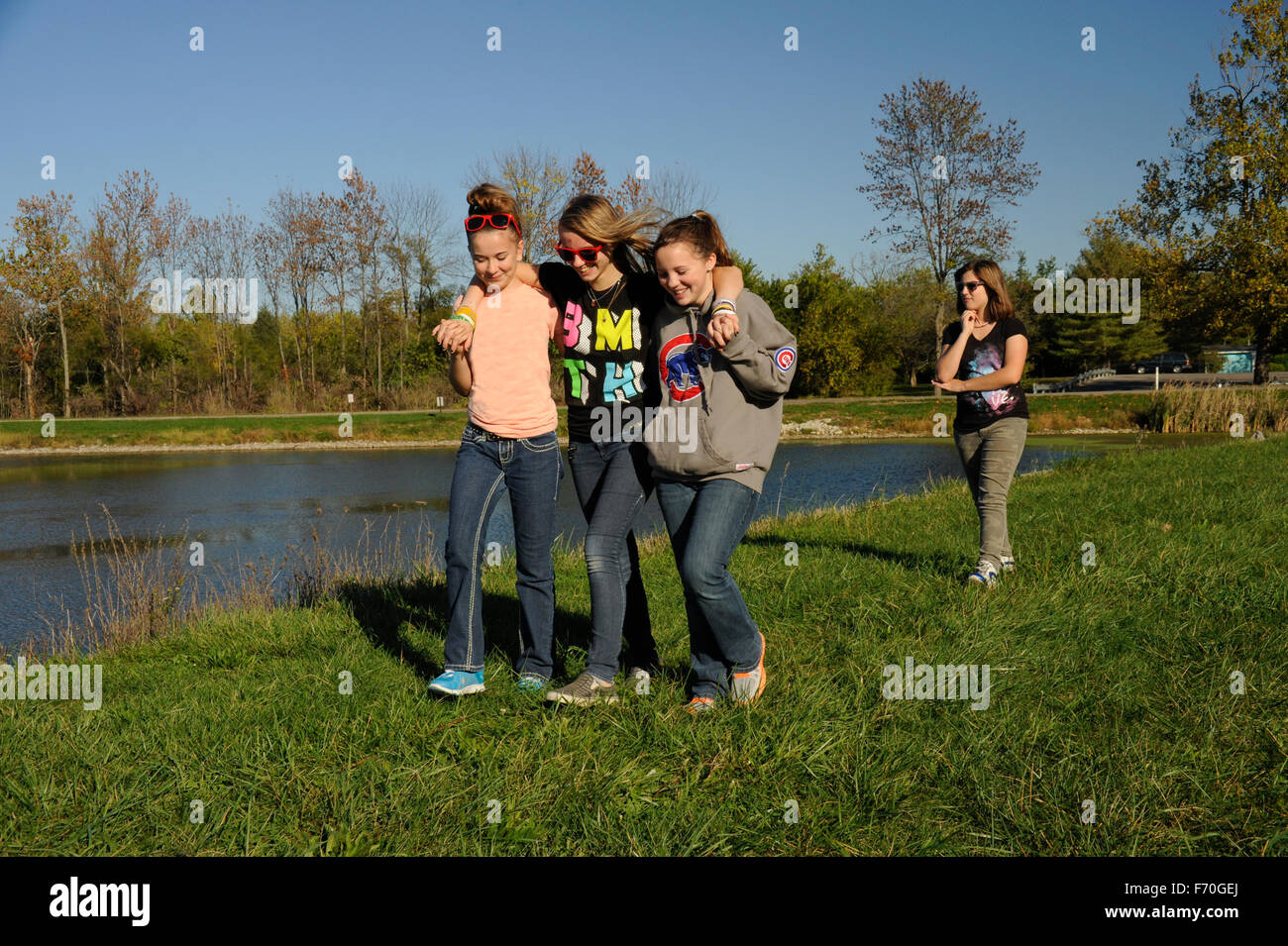 Three teen girls ignoring one girl - Stock Image