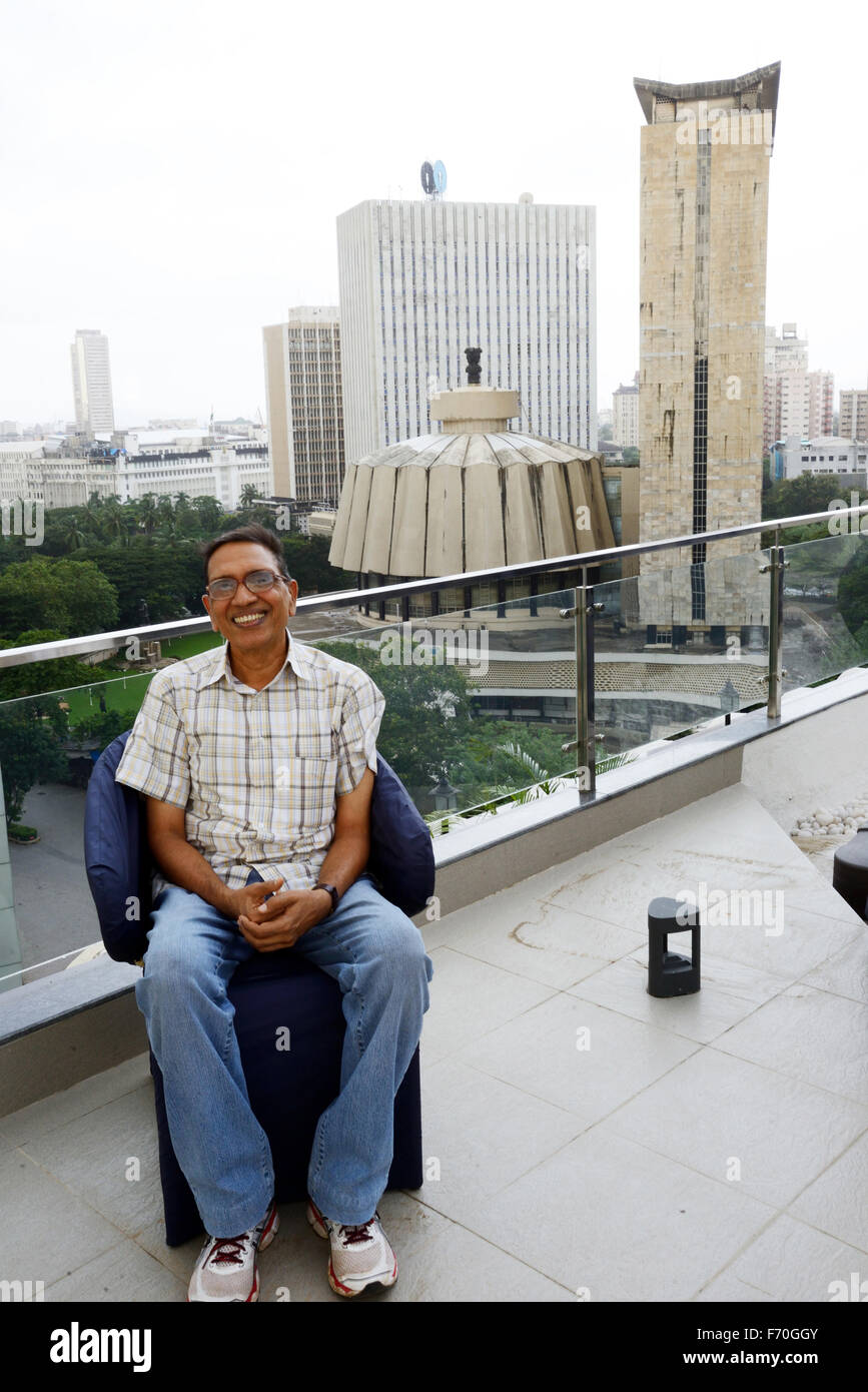 Jagdish Agarwal founder of Dinodia Photo Library sitting on the terrace of new office at Nariman Point in front - Stock Image