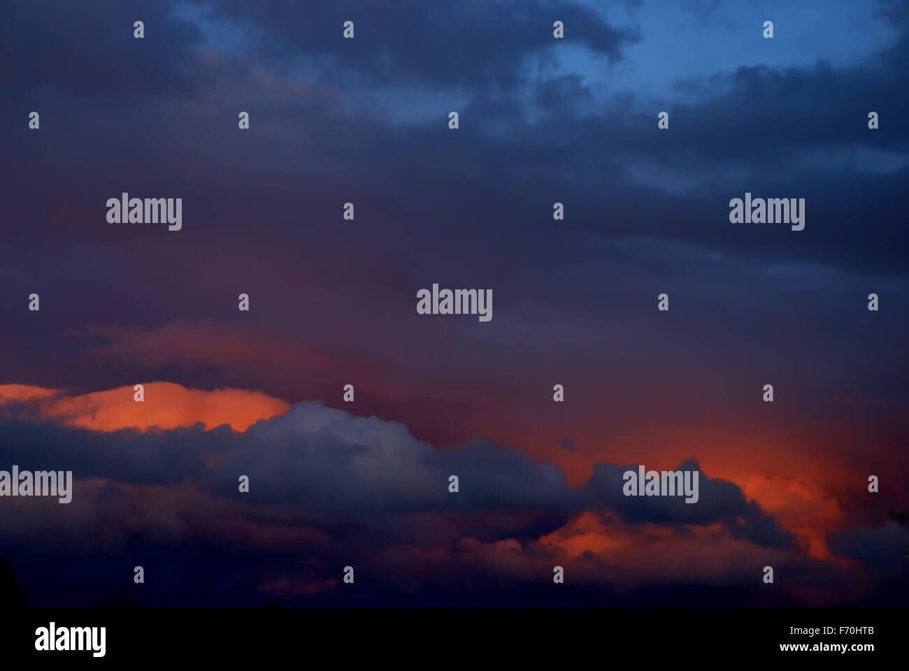 Storm clouds at sunset in purple, orange, pink, blue - Stock Image