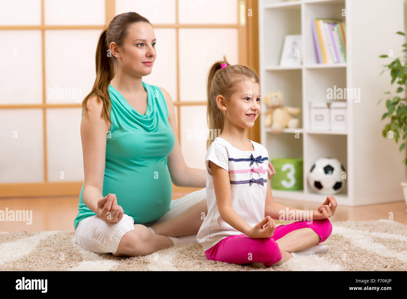 Pregnant mother and child do yoga, relax in lotus position on fit mat at home - Stock Image