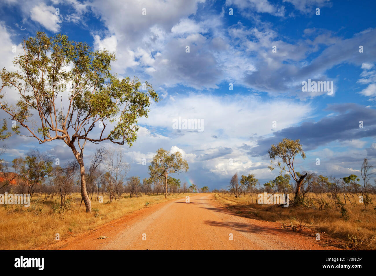 An unsealed road through the Australian outback with a rainbow at the end of the road. Photographed in the Purnululu - Stock Image