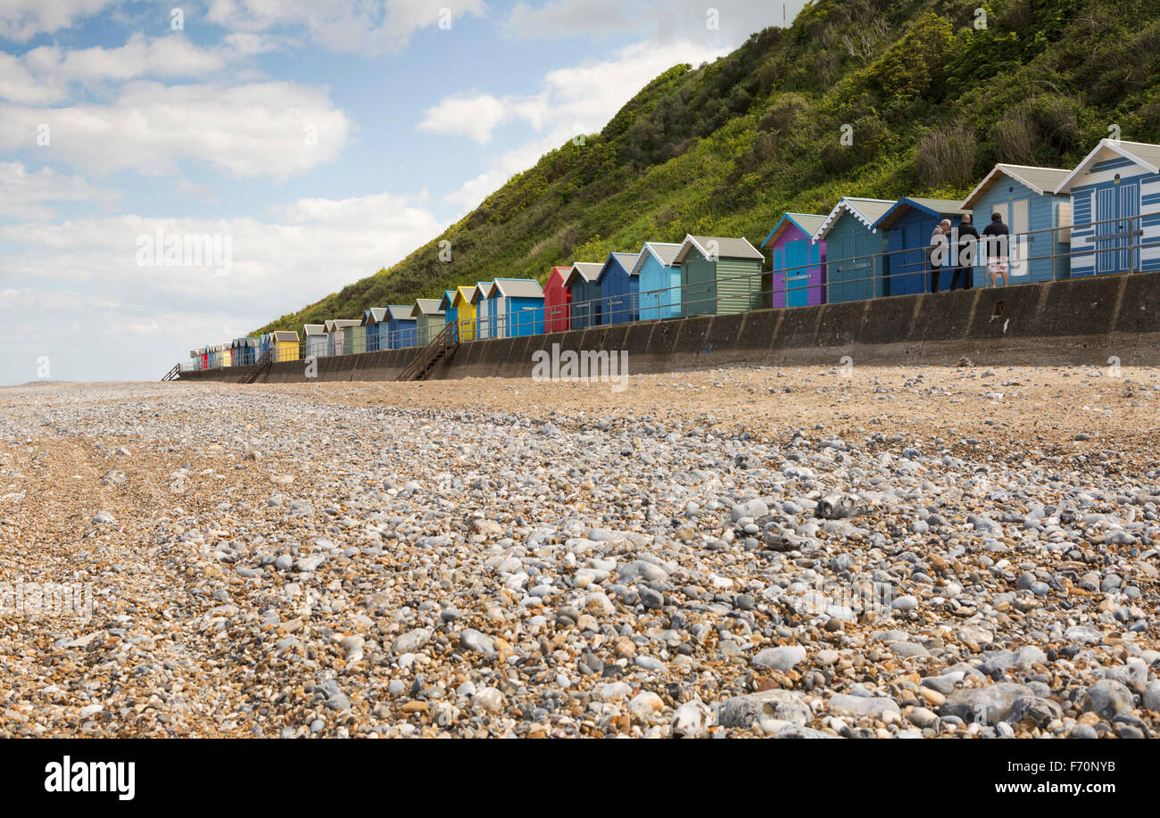 beach huts in front of cliffs at Cromer, Norfolk, UK, sunny day with blue sky and clouds in landscape orientation. - Stock Image