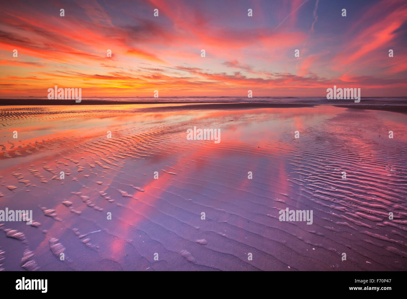 Beautiful sunset and reflections on the beach at low tide. - Stock Image