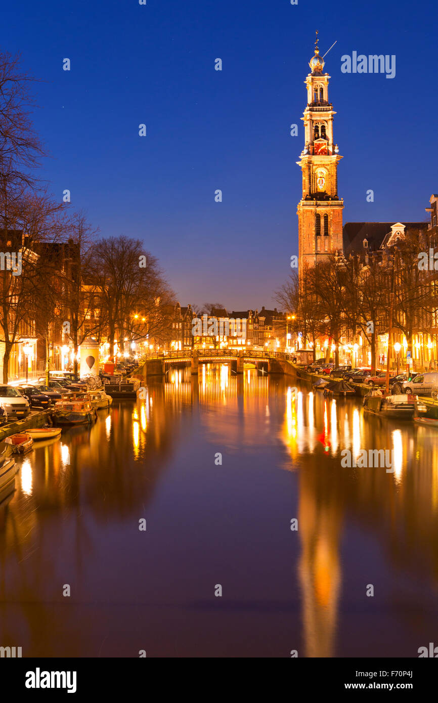 The Westerkerk (Western Church) along the Prinsengracht canal in Amsterdam at night. - Stock Image