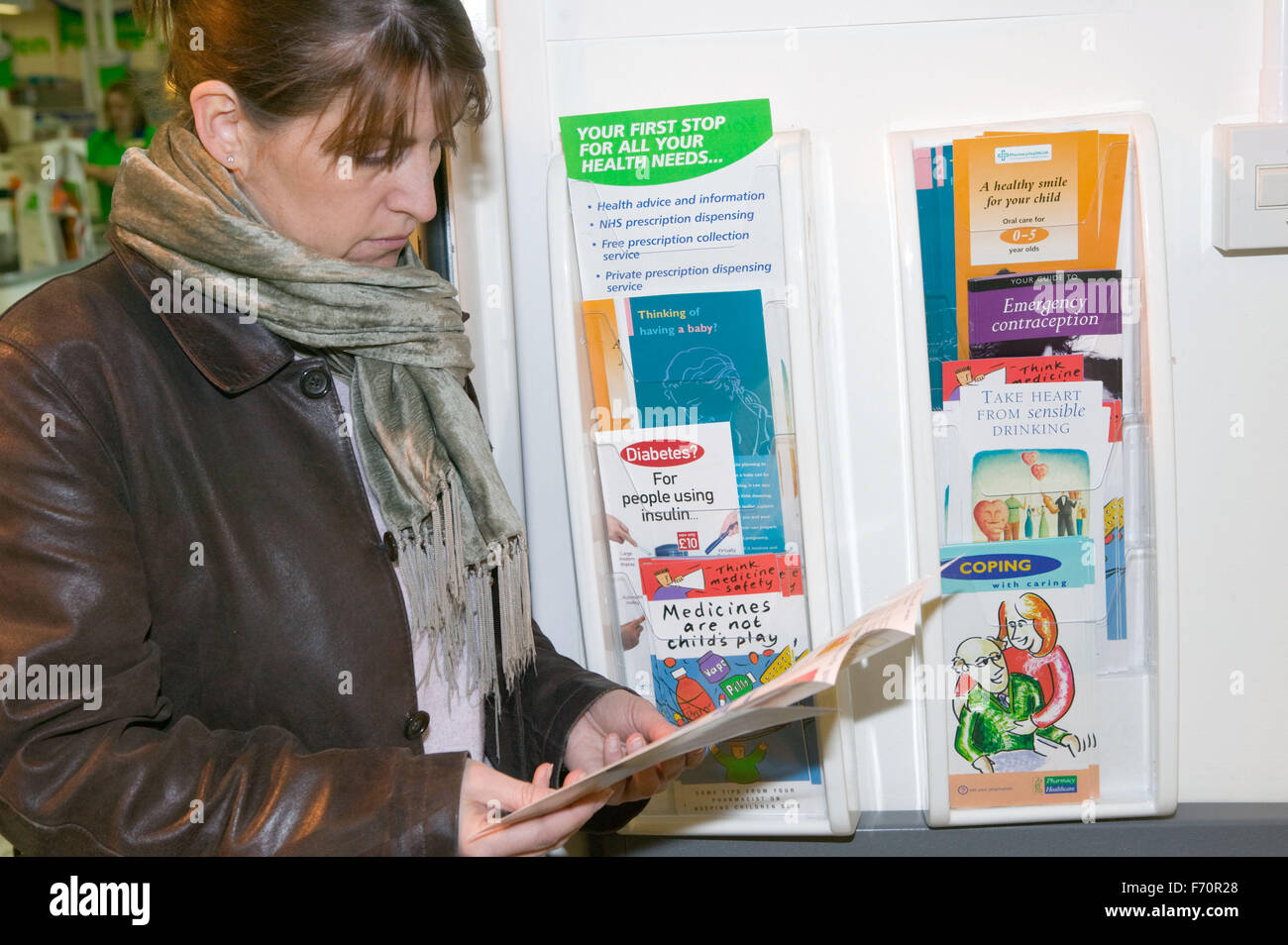 Woman looking through health leaflets available at a supermarket pharmacy, - Stock Image
