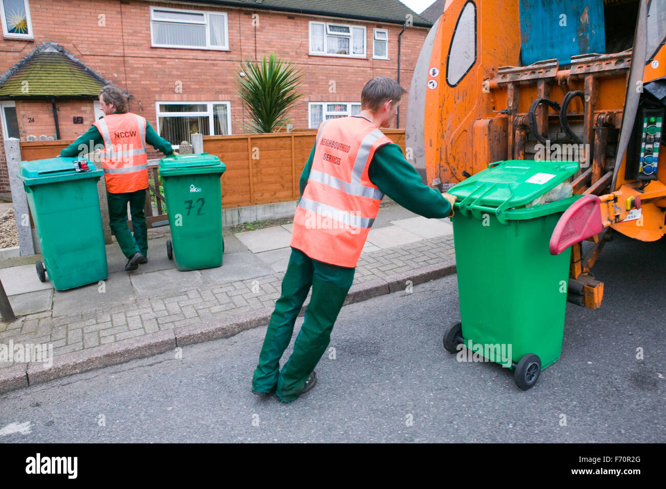 Binmen collecting refuse from neighbourhood wheelie bins and loading them into dust cart, - Stock Image