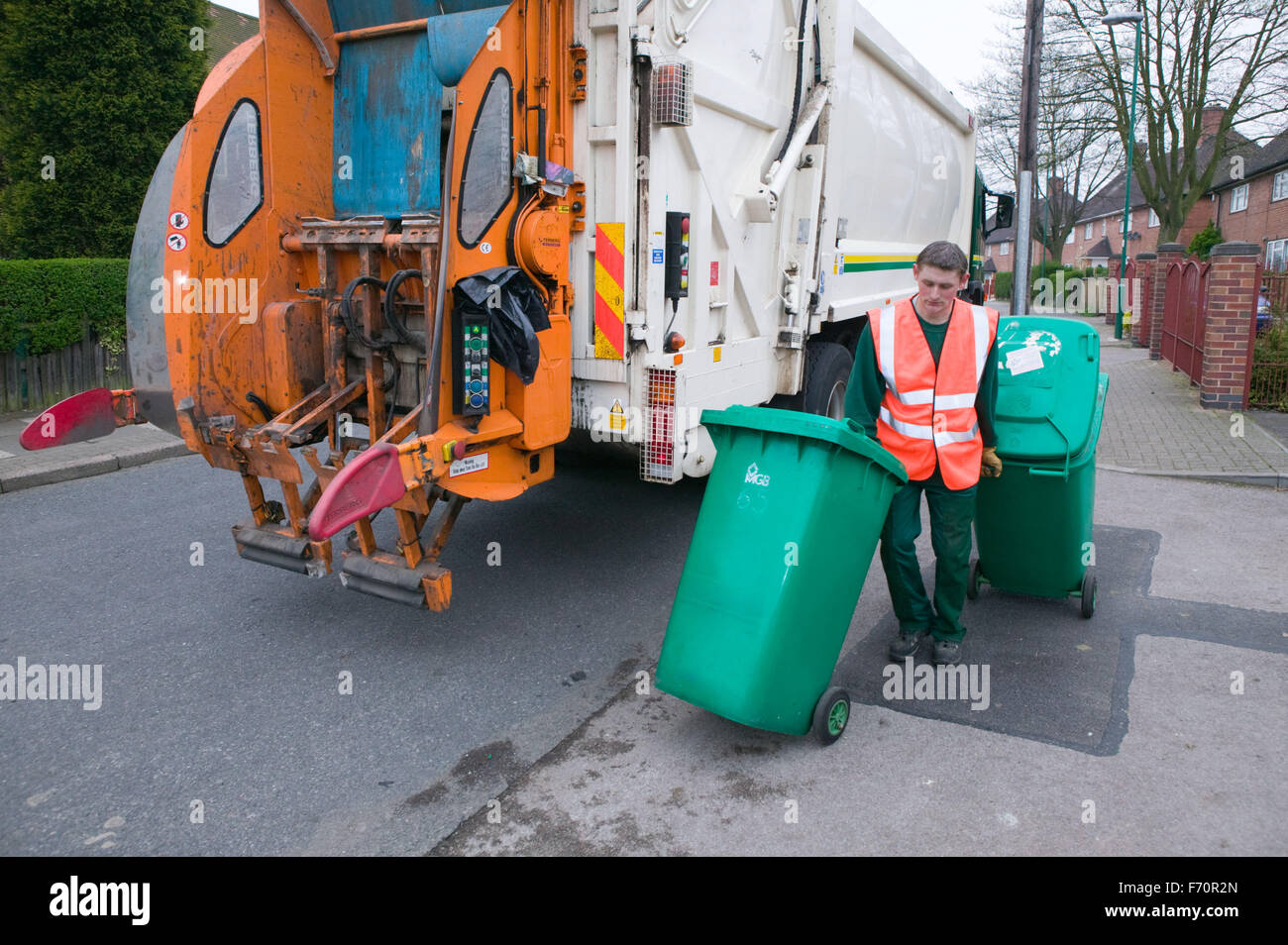 Binman collecting refuse from neighbourhood wheelie bins and loading them into dust cart, - Stock Image