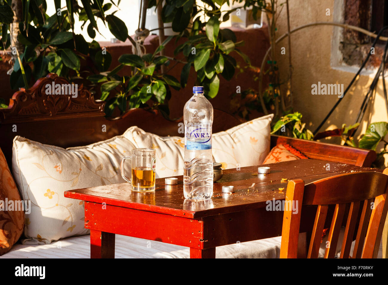 Santorini. Still life, close up of table outside Greek taverna, with water bottle and glass mug half full with beer - Stock Image