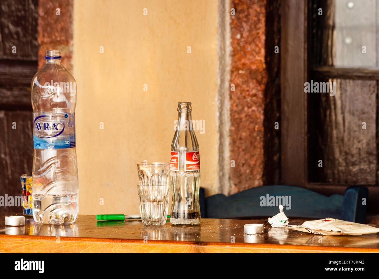 Santorini. Still life, close up of table outside Greek taverna, with water bottle, coca-cola bottle, glasses and Stock Photo