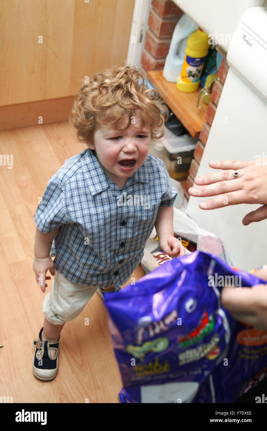 Toddler having a temper tantrum after being refused a packet of crisps, - Stock Image