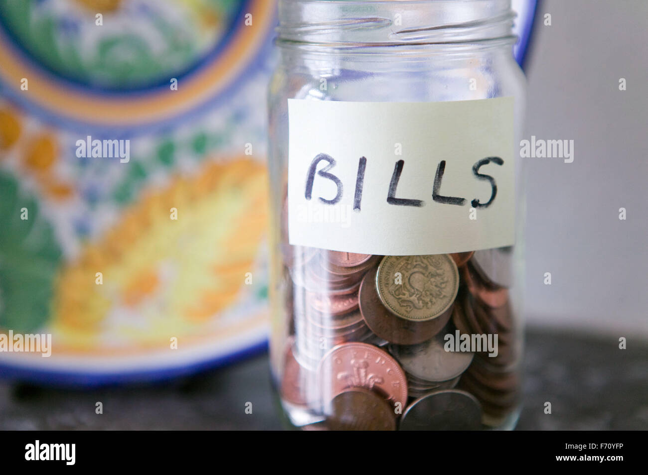 Jar of pennies saved for paying household bills, - Stock Image