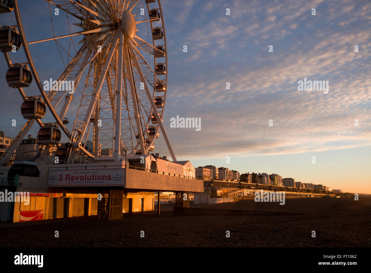 Brighton ferris wheel and Kemptown seafront illuminated by the rising sun - Stock Image