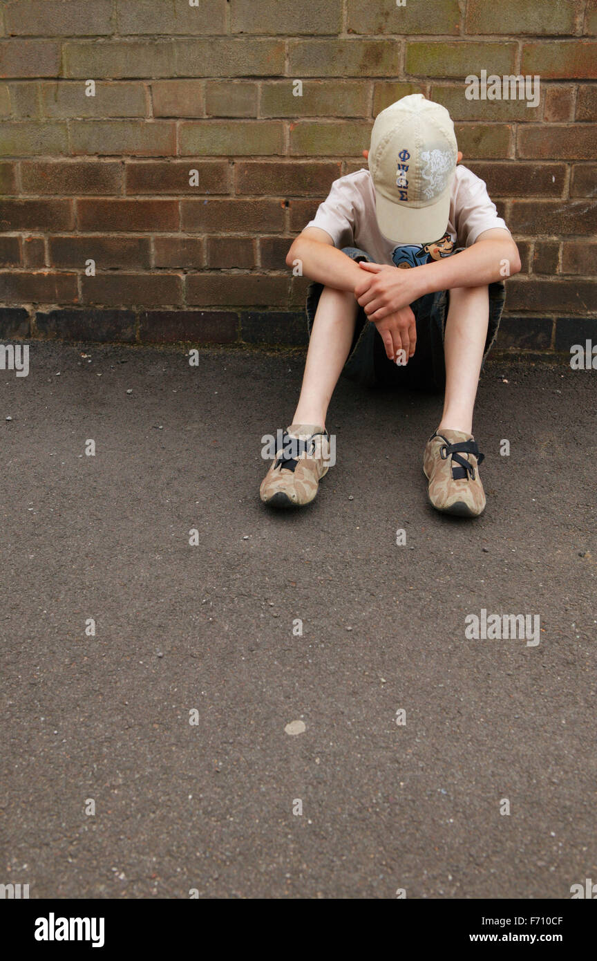 Boy sitting by side of wall with his head bowed, - Stock Image