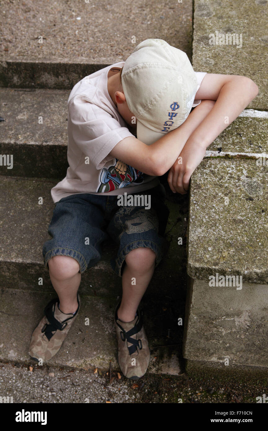 Boy sitting on steps with his head bowed, - Stock Image